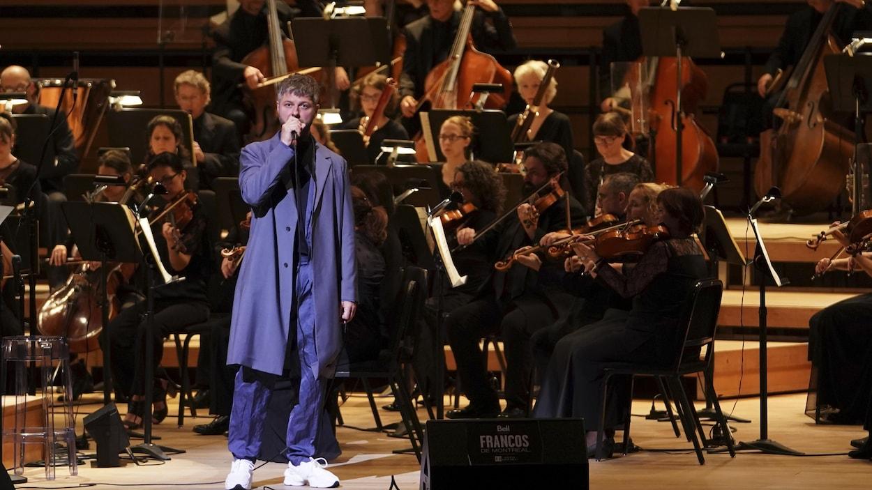 Un chanteur est accompagné d'un orchestre complet sur scène.