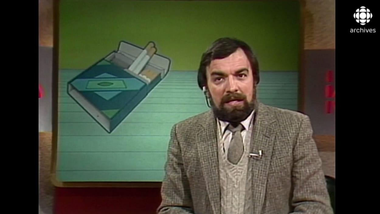 Le présentateur est devant une illustration d'un paquet de cigarettes.