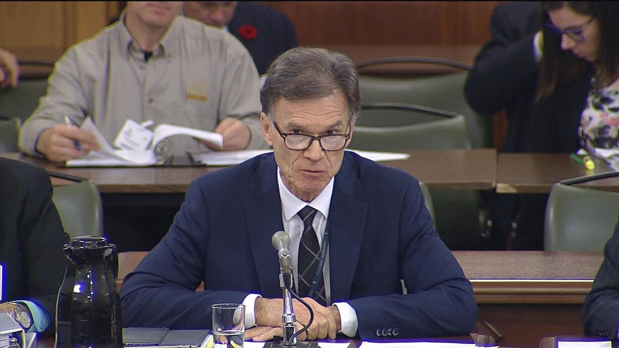 Pierre Reid, assis, derrière un micro.