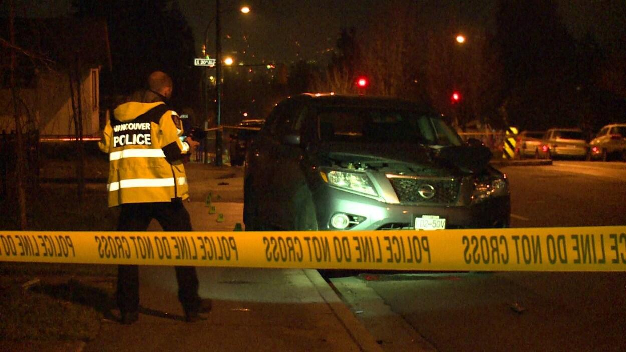 Un policier est debout devant le VUS Nissan qui a heurté un piéton samedi soir à Vancouver.