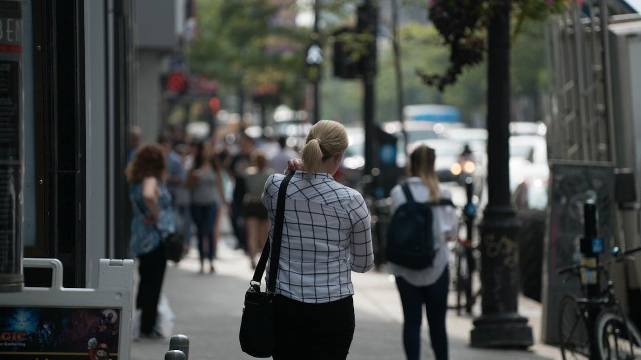 Une femme marche sur la rue Sainte-Catherine à Montréal.