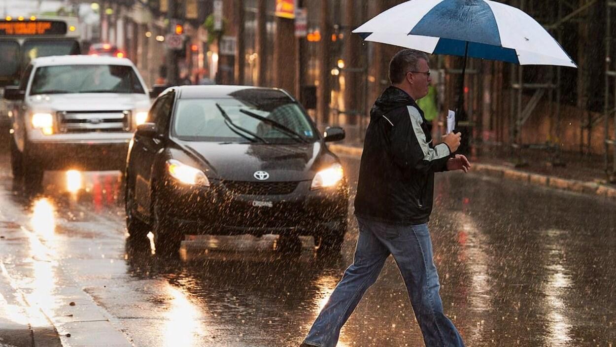 Un piéton traverse la rue sous la pluie, un parapluie à la main.