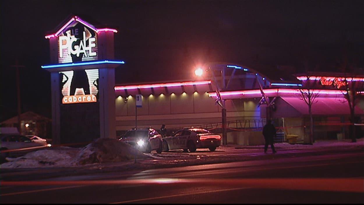 Une photo du club Le Pigale prise la nuit, deux voitures de police et deux silhouettes dans le stationnement