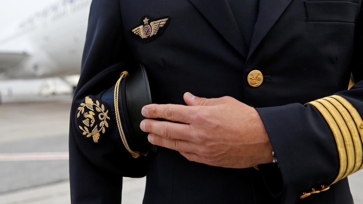 Un homme en tenue de pilote de l'aviation civile tient une casquette sous le bras.