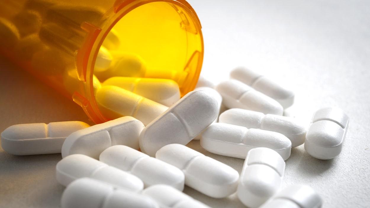 Des pilules sorties d'un flacon, dispersées sur une surface.