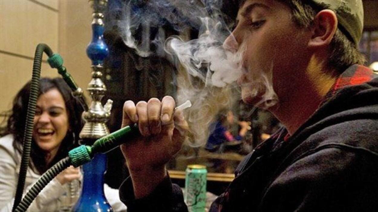 Un jeune homme fume un narguilé dans un bar. Une jeune femme rit en arrière plan.