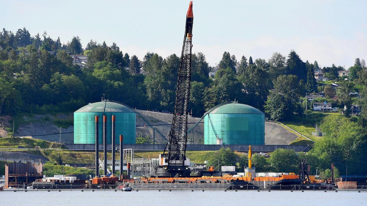 Vue panoramique du terminal, avec une grue et deux réservoirs de pétrole.