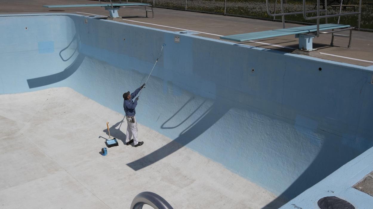 Un employé repeint l'intérieur d'une grande piscine publique.