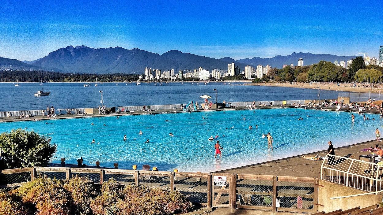 Des gens nagent dans une grande piscine extérieure avec vue sur le centre-ville de Vancouver, la plage, l'eau et les montagnes au loin.