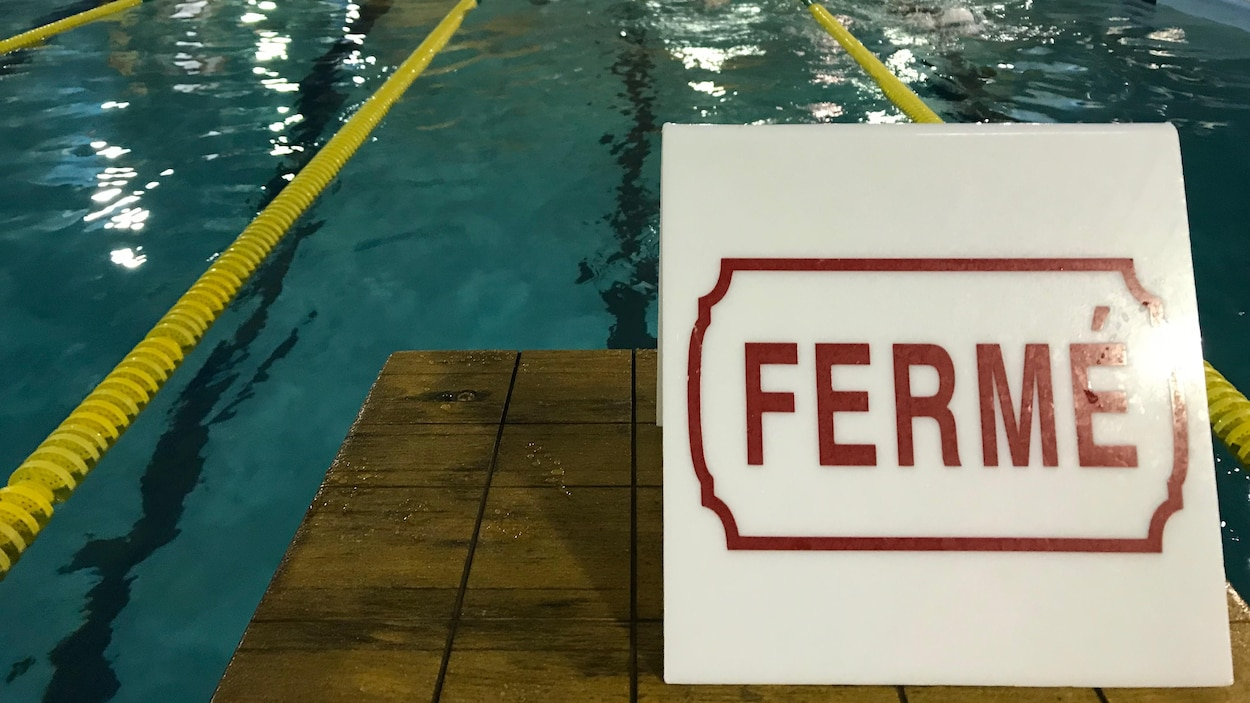 Vue sur les corridors d'une piscine intérieure avec une affiche où il y est inscrit « fermé » en rouge.
