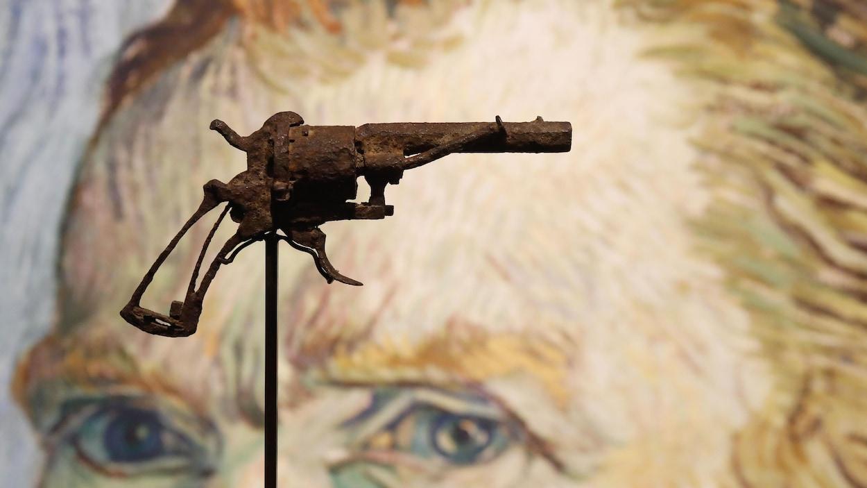 Un revolver très rouillé est posé sur un support en métal, devant une image d'un autoportrait de Vincent Van Gogh.