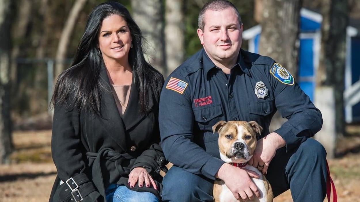 Une femme et un homme posent avec un chien en extérieur.