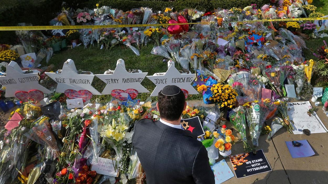 Un homme portant une kippa est vu de dos. Il est debout devant des dizaines de bouquets de fleurs et des étoiles en carton au nom des victimes.