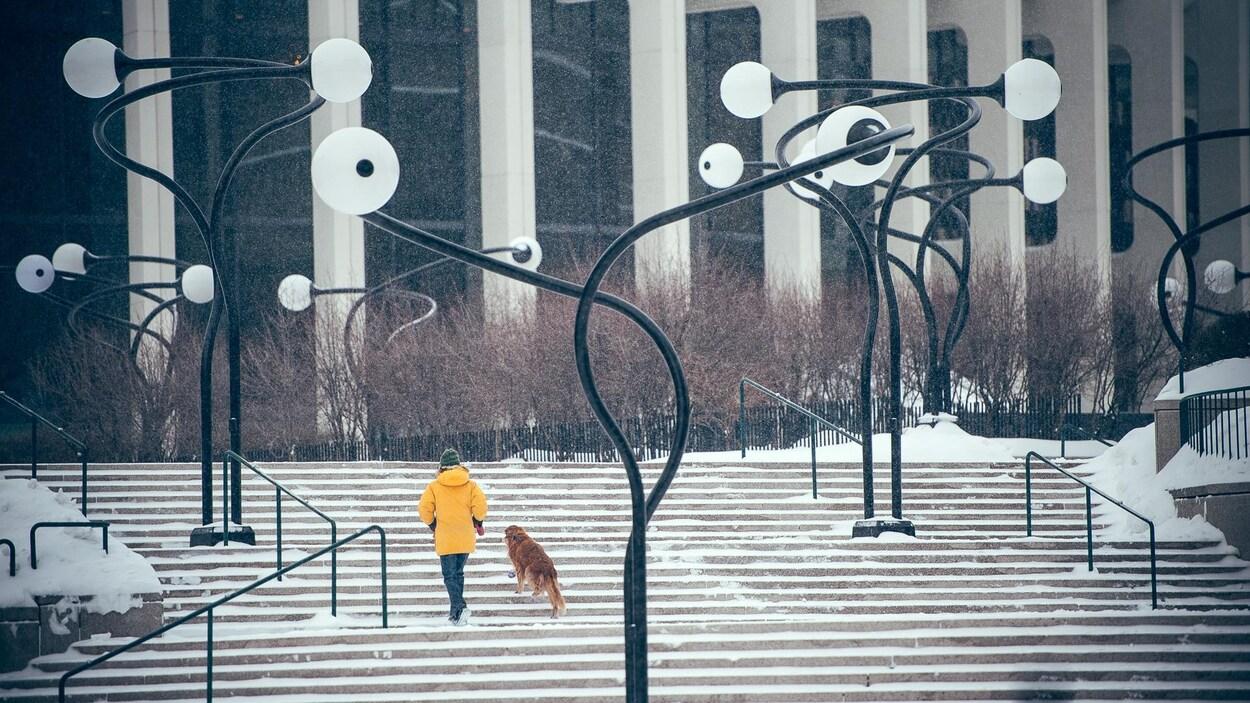 Un piéton marche avec son chien sur l'esplanade de la Place des Arts, sous la neige, au centre-ville de Montréal.