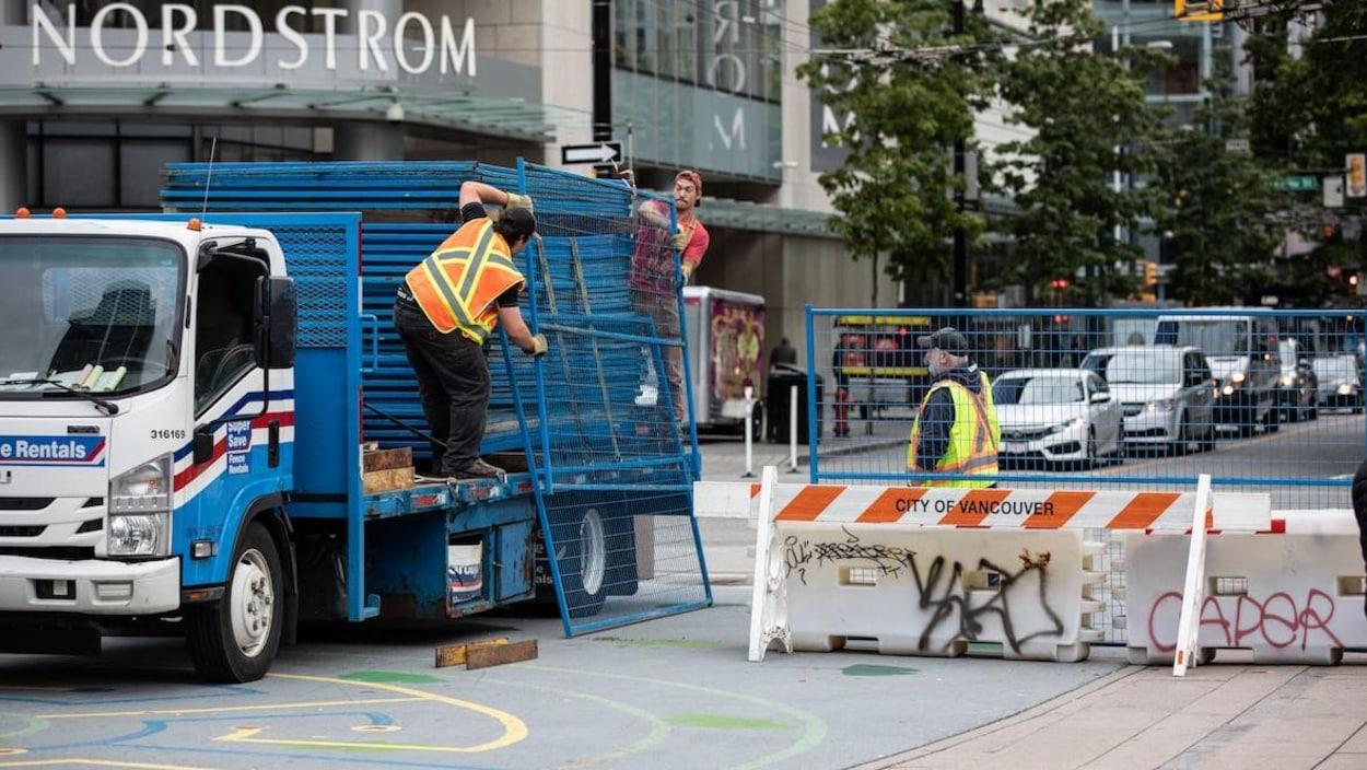 Deux hommes descendent un panneau de clôture grillagée temporaire d'un camion, un troisième homme les observe.
