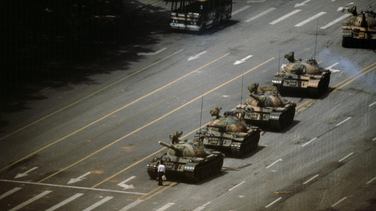 Un homme portant une chemise blanche est debout face à cinq chars d'assaut sur une avenue.