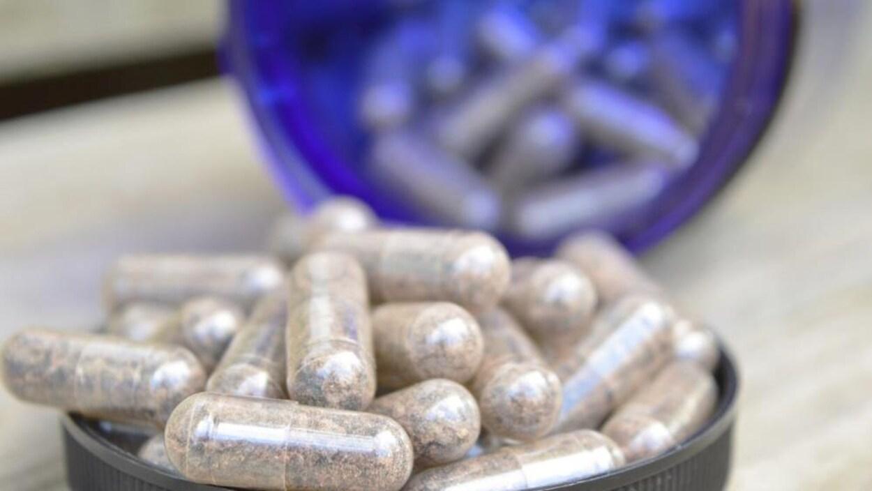 Des capsules pleines, dans le couvercle d'une petite bouteille de pilules, en arrière-plan, le reste de la bouteille.