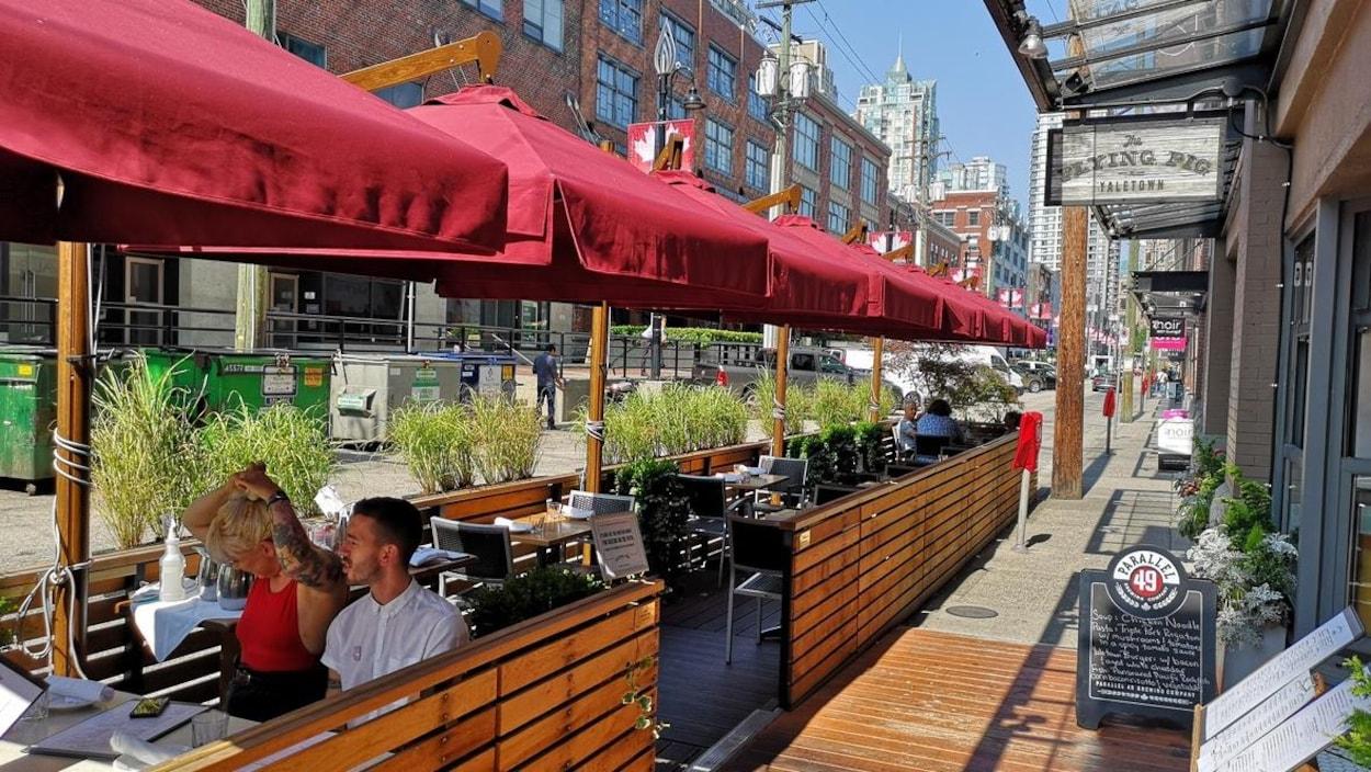 À droite, un restaurant, à gauche, une terrasse en bois avec des parasols qui empiète dans la rue, où on voit deux clients. En arrière, on voit des plantes qui la séparent de la rue.