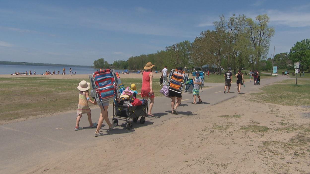 Des adultes et des enfants marchent sur une piste cyclable près de la plage du parc des Cèdres.