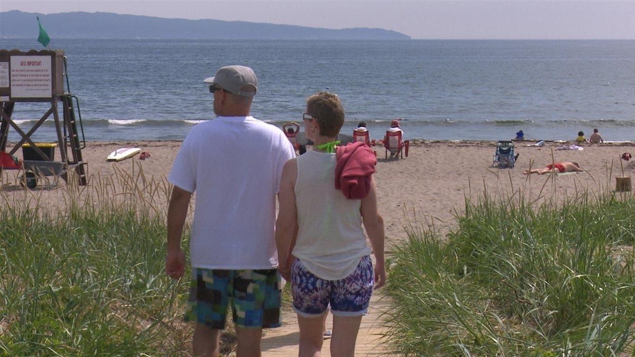 Un homme et une femme marchent vers une plage où se trouvent aussi d'autres personnes qui profitent des lieux.