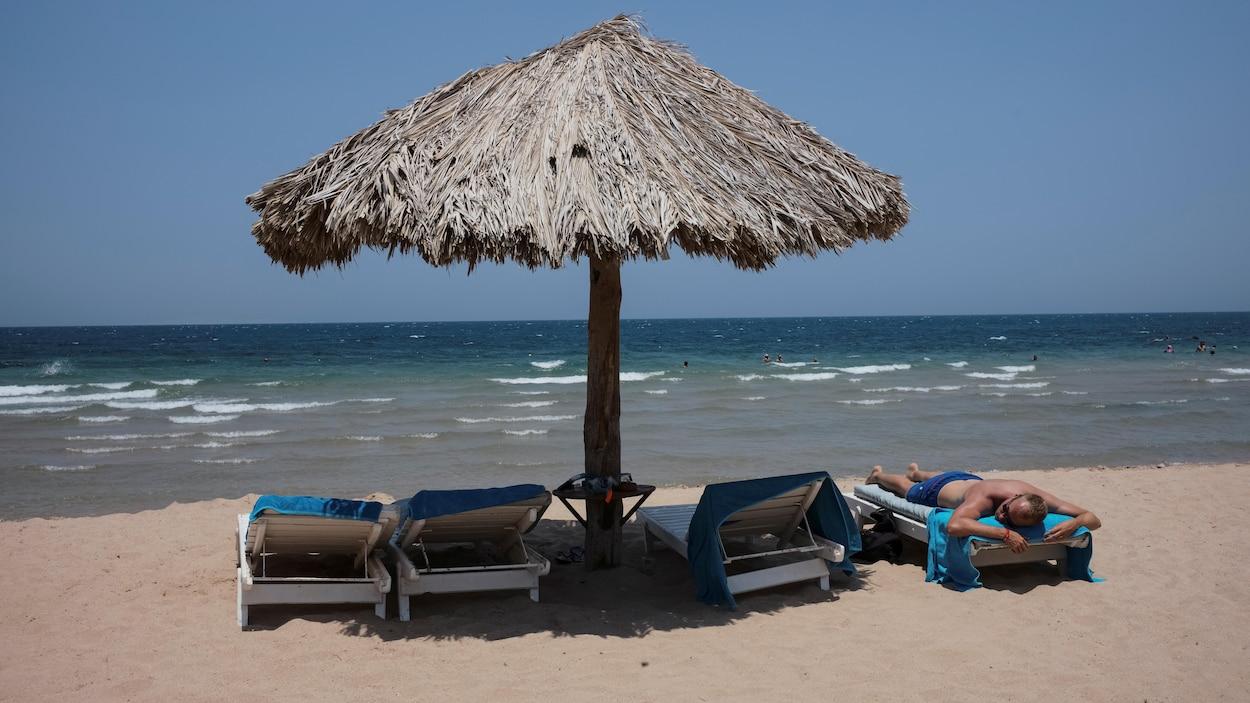 Un homme se fait bronzer sur la plage.