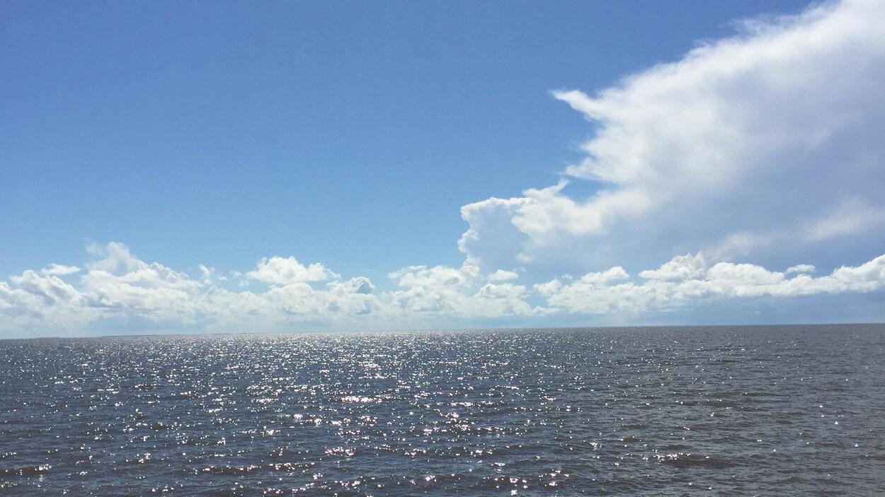 Une grande étendue d'eau, le lac Winnipeg, sous un ciel ensoleillé avec quelques nuages.