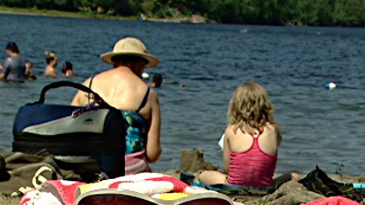 Une femme et une fillette sont assises côte à côte et construisent un château de sable.