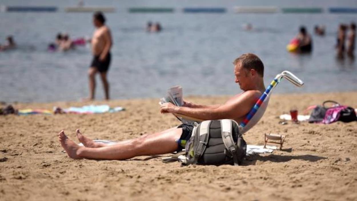 Un homme assis sur une chaise de plage, à la plage de Mooney's Bay à Ottawa.