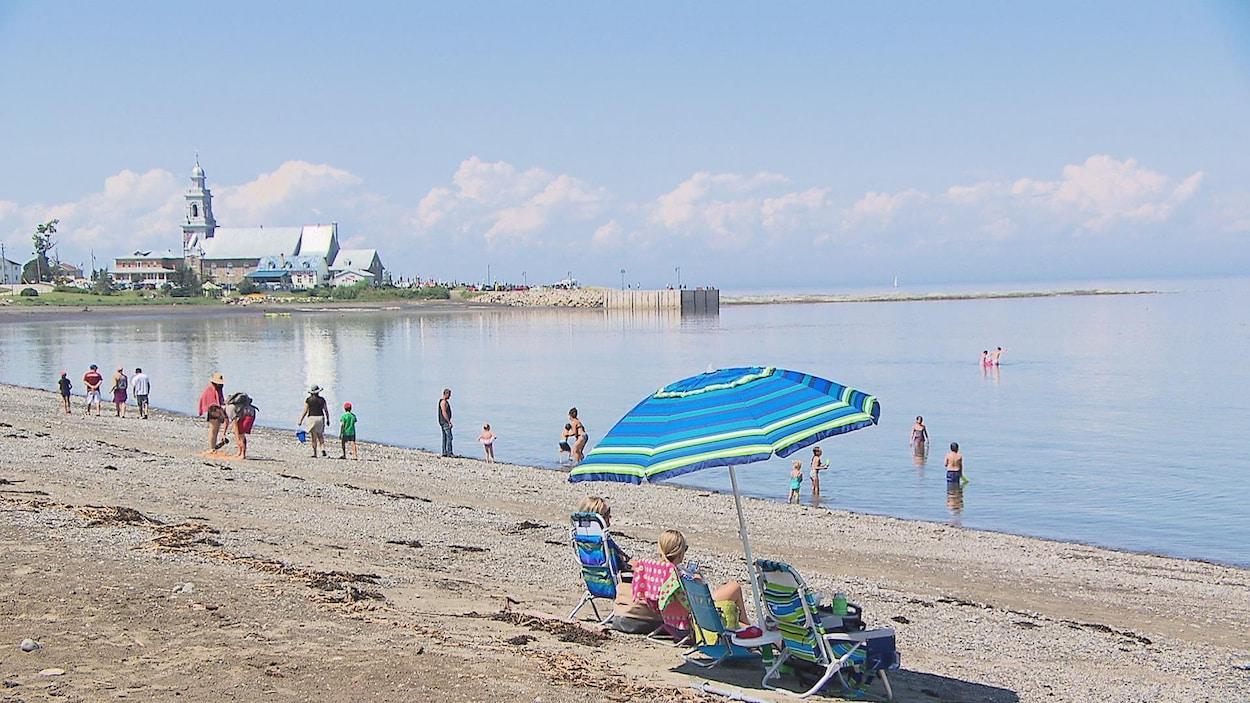 Une dizaine de personnes profitent de la plage, des enfants se baignent tandis que deux femmes se reposent sous un parasol bleu.
