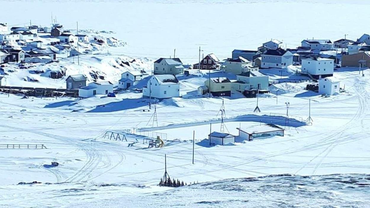 Le village de Harrington Harbour sur la Basse-Côte-Nord en février 2018 photographié d'un peu plus haut sur la rive. On peut y apercevoir la patinoire et quelques maisons et au loin le fleuve.