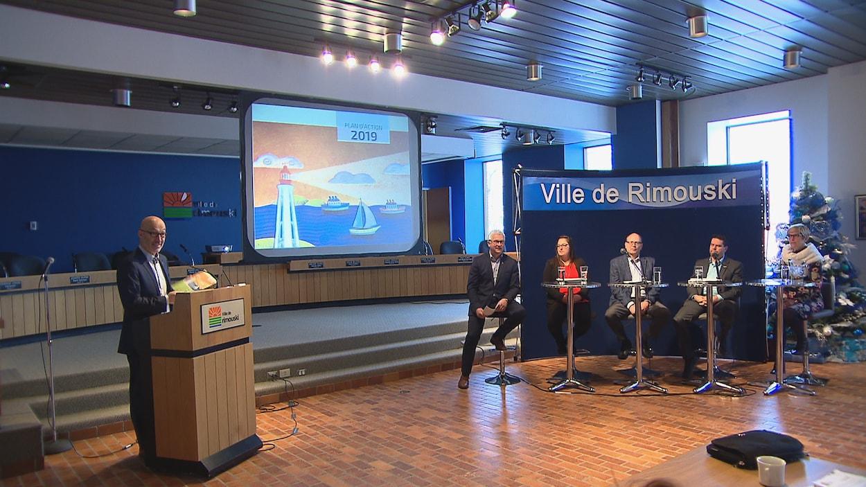 Le maire présente au micro le document et les autres élus sont assis à droite.