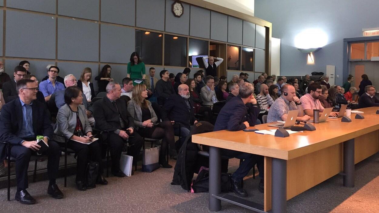 De nombreuses personnes sont assises dans le fond de la salle.