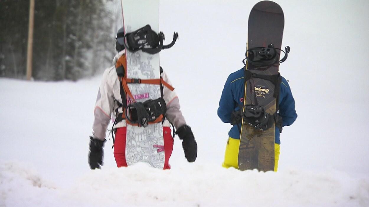 Deux planchistes transportant leurs planches sur leurs dos.