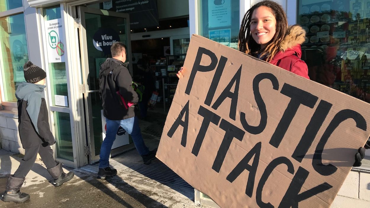 Une étudiante tient une pancarte « Plastic Attack » à l'entrée d'un IGA.