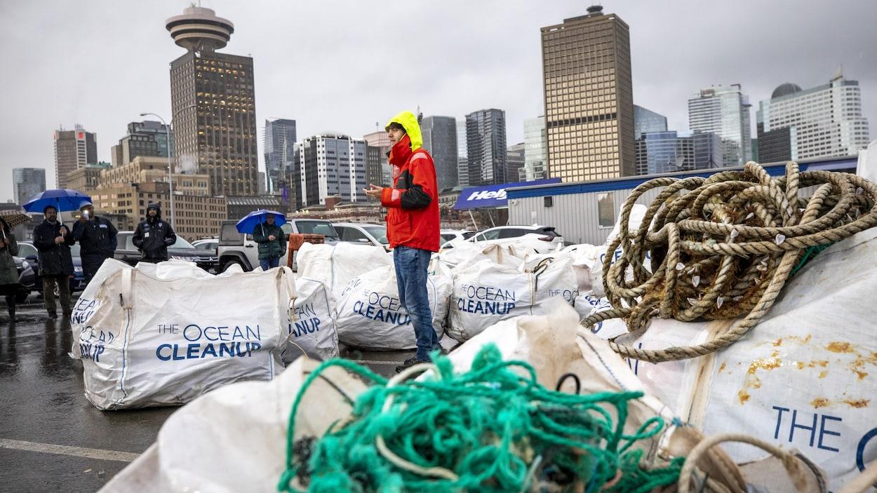 Une personne entourée de sacs pleins de plastique s'adresse à un petit rassemblement de personnes sous la pluie.