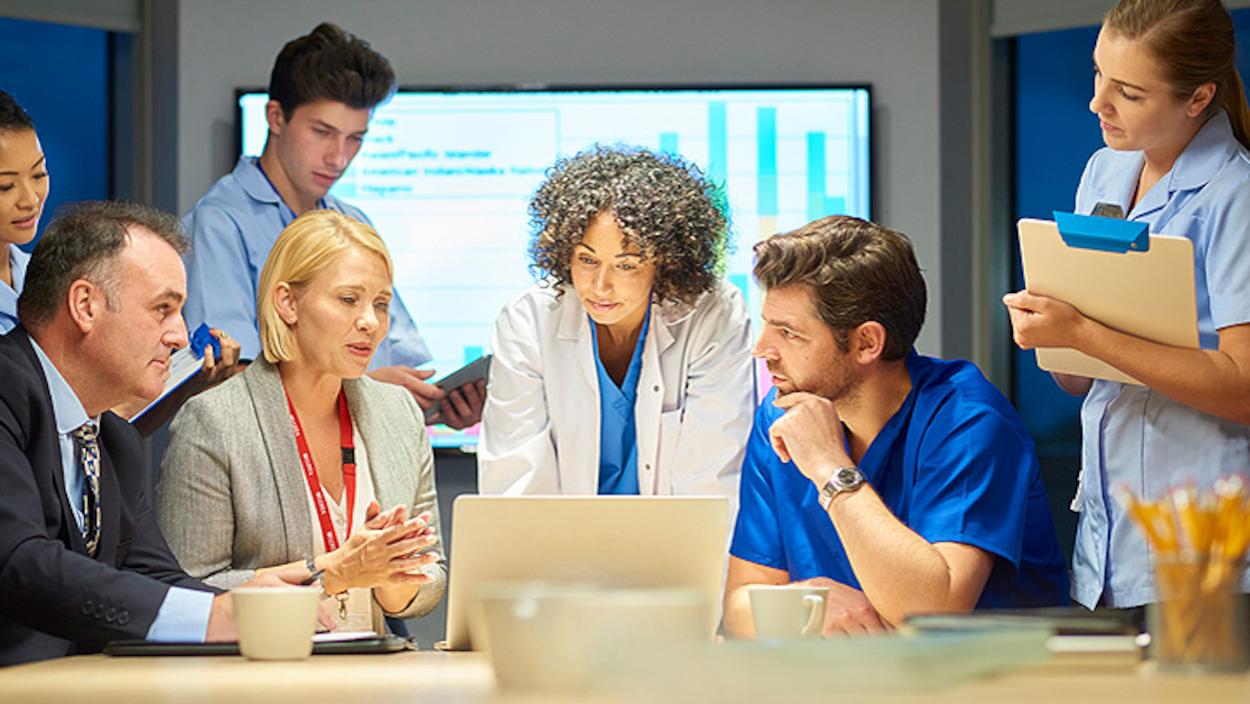 Plusieurs personnes discutent devant un écran d'ordinateur. Toutes sont en tenue de travail d'entreprise ou médicale.