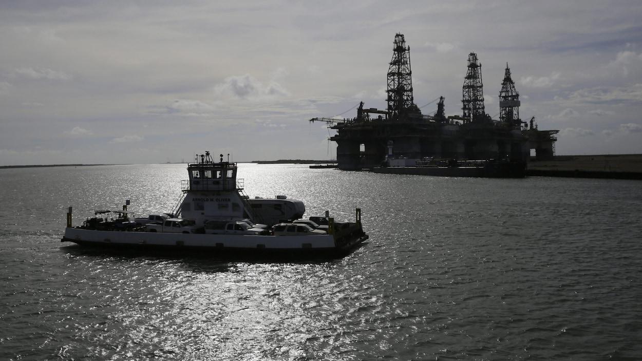 Un traversier évacuant des résidents de Port Aransas, au Texas, passe devant une plateforme pétrolière.