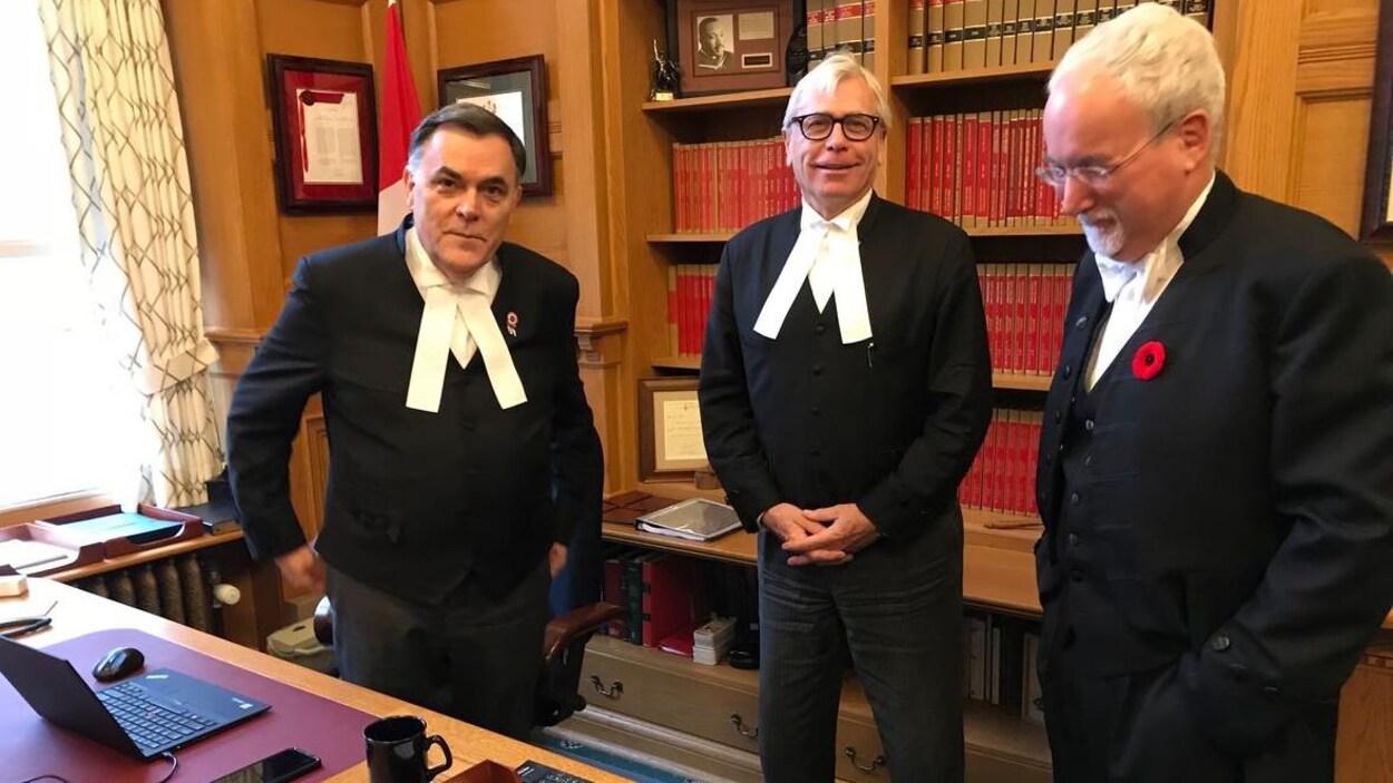 Darryl Plecas, Craig James et Gary Lenz debout dans un bureau de l'Assemblée législative.