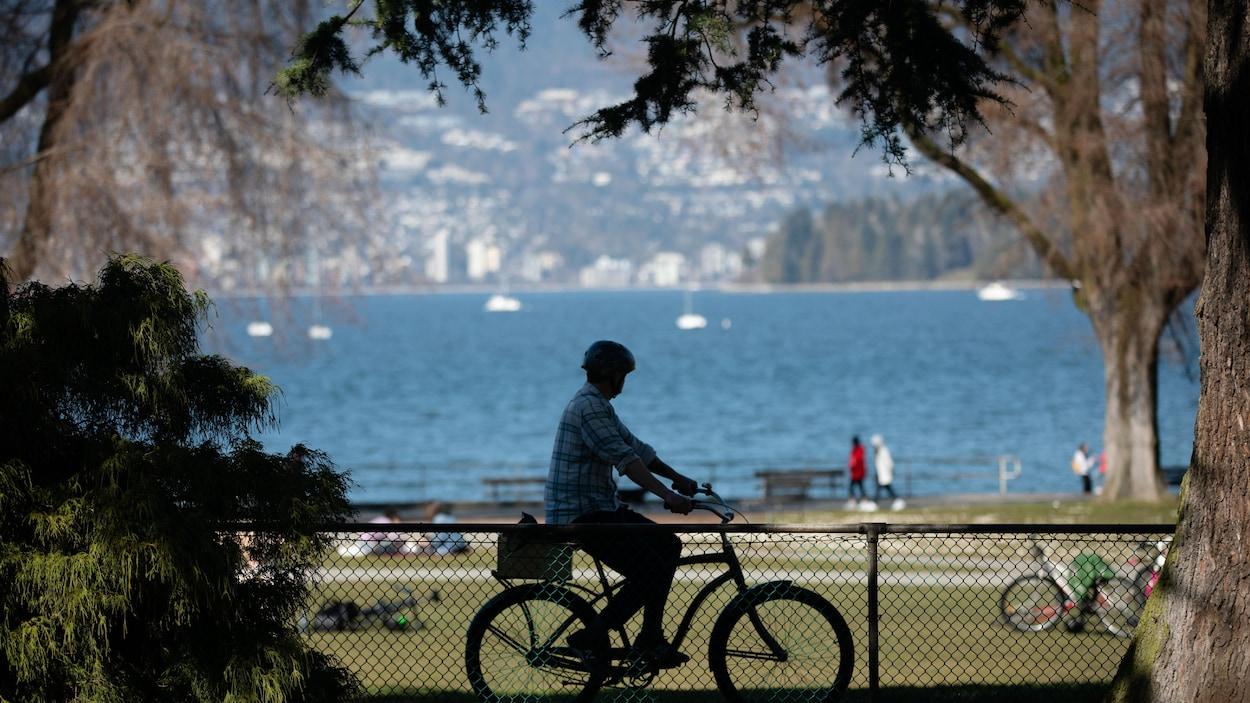 Un homme fait du vélo devant la plage de Kitsilano à Vancouver.