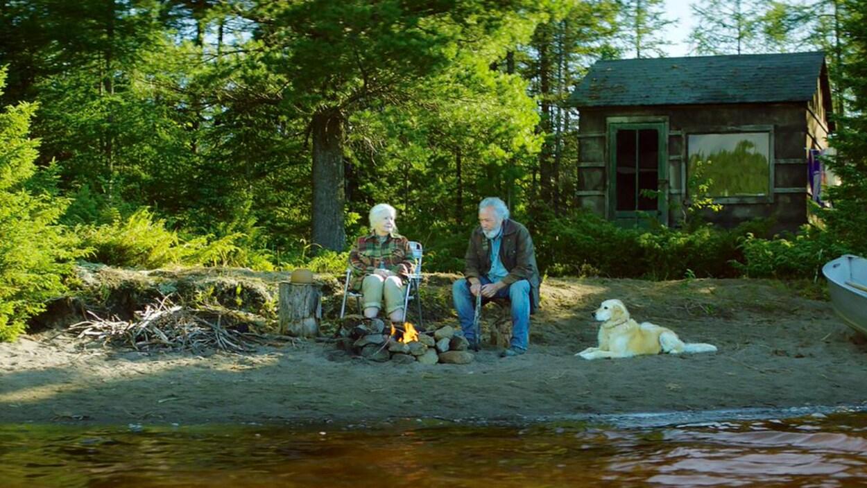 Un homme et une femme sur le bord d'une rivière avec un chien.