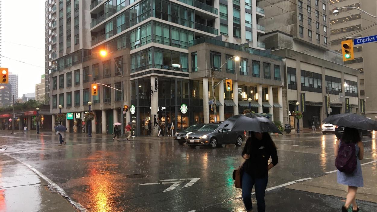 La pluie tombe, mercredi matin, à l'intersection des rues Charles et Bay au centre-ville de Toronto.