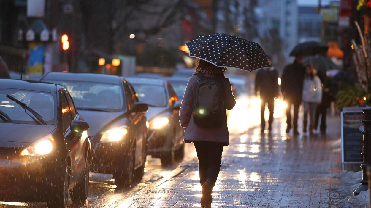 Des passants marchent sur le trottoir de la rue St-Jean, à Québec, protégés par leur parapluie. La lumière des phares des voitures se reflète sur la surface mouillée.