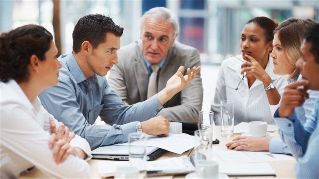Six personnes sont assises autour d'une table et discutent.