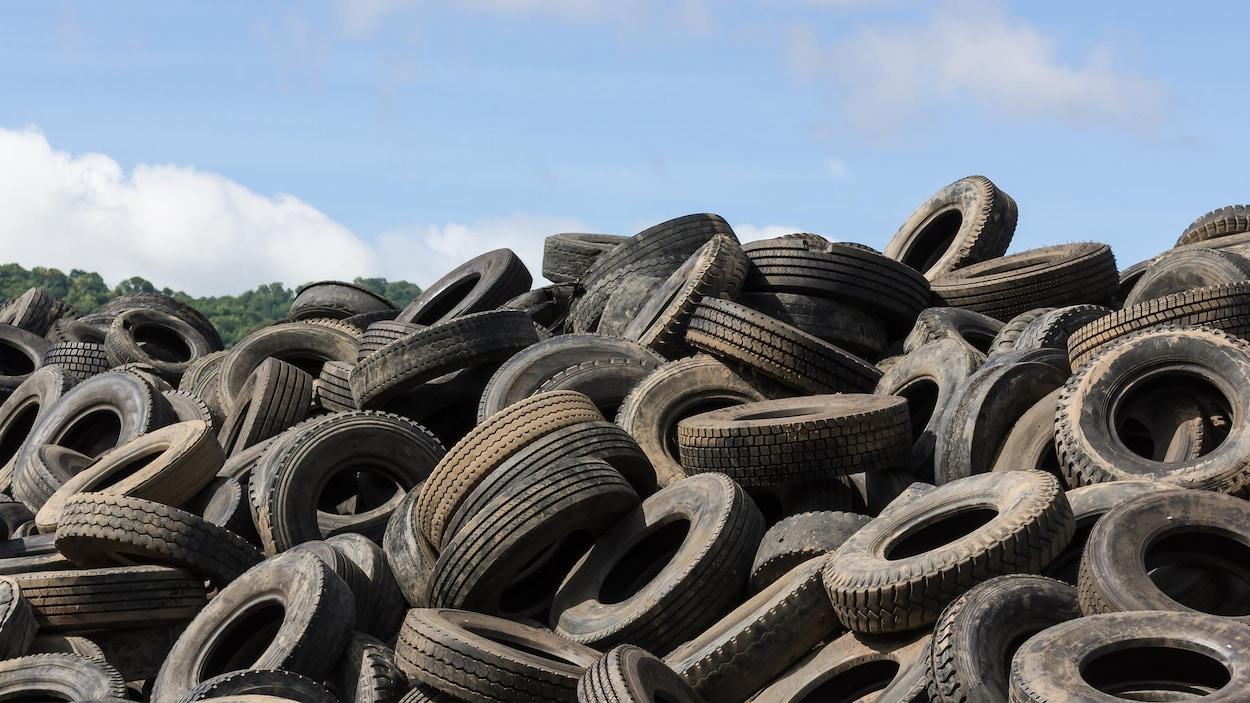 Amas de pneus usagés sur le terrain d'une entreprise de recyclage.
