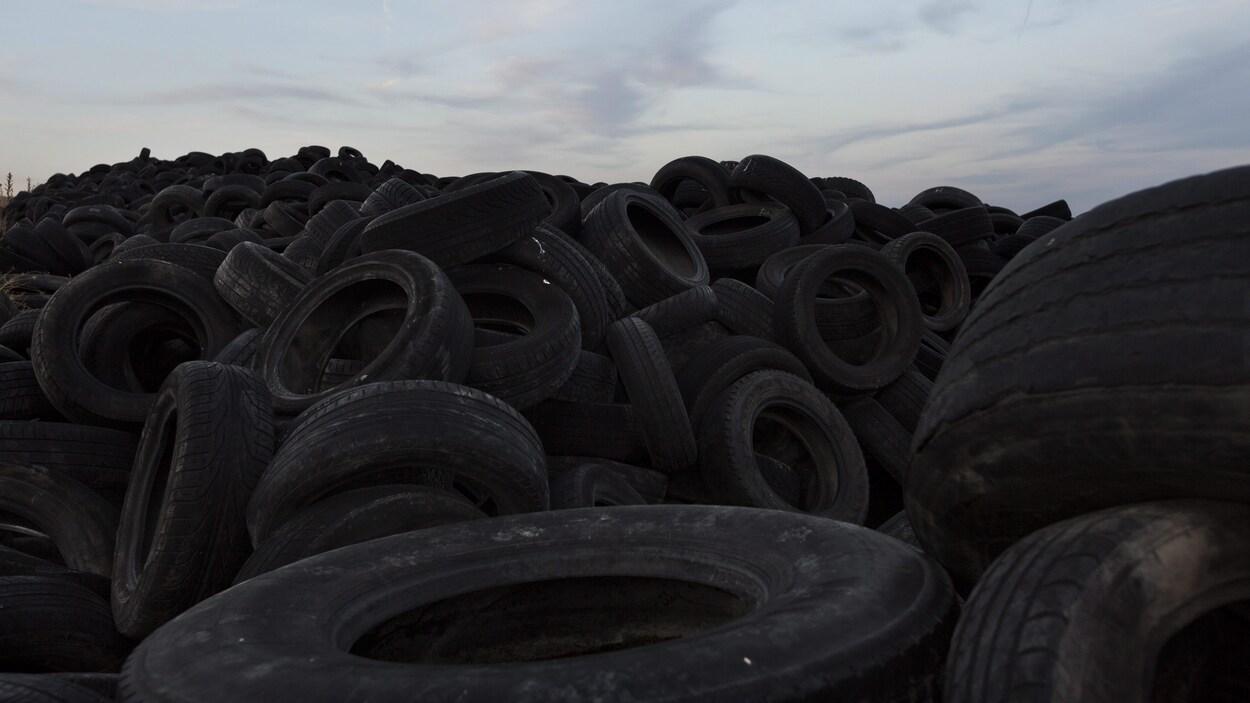 Une montagne de pneus usés dans un dépotoir.