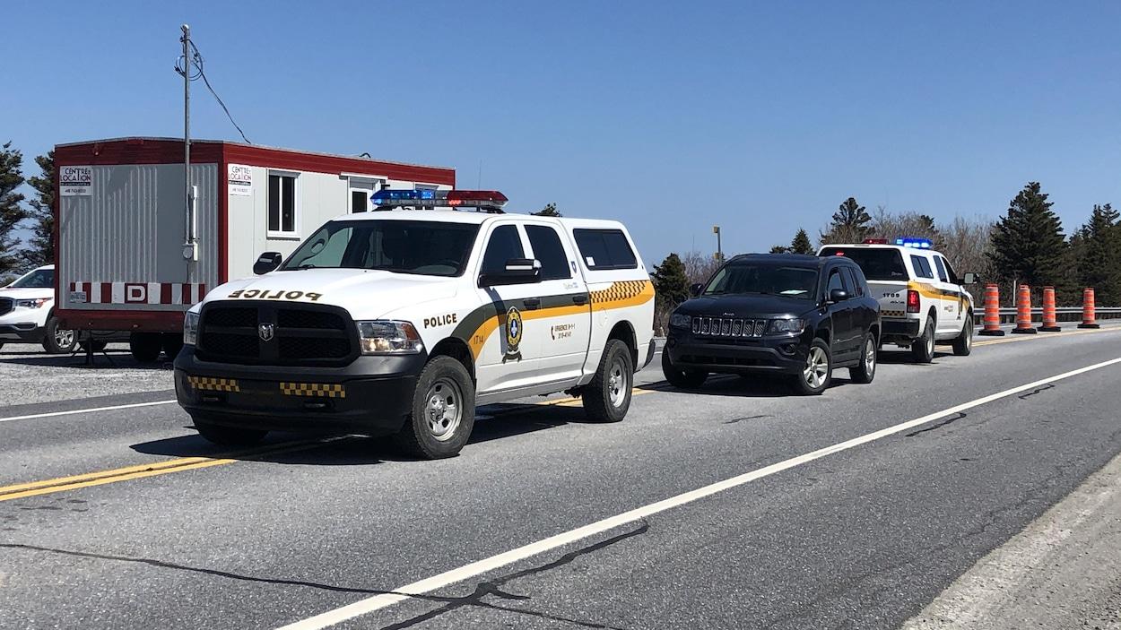 Des véhicules de police sont stationnés devant des cônes.