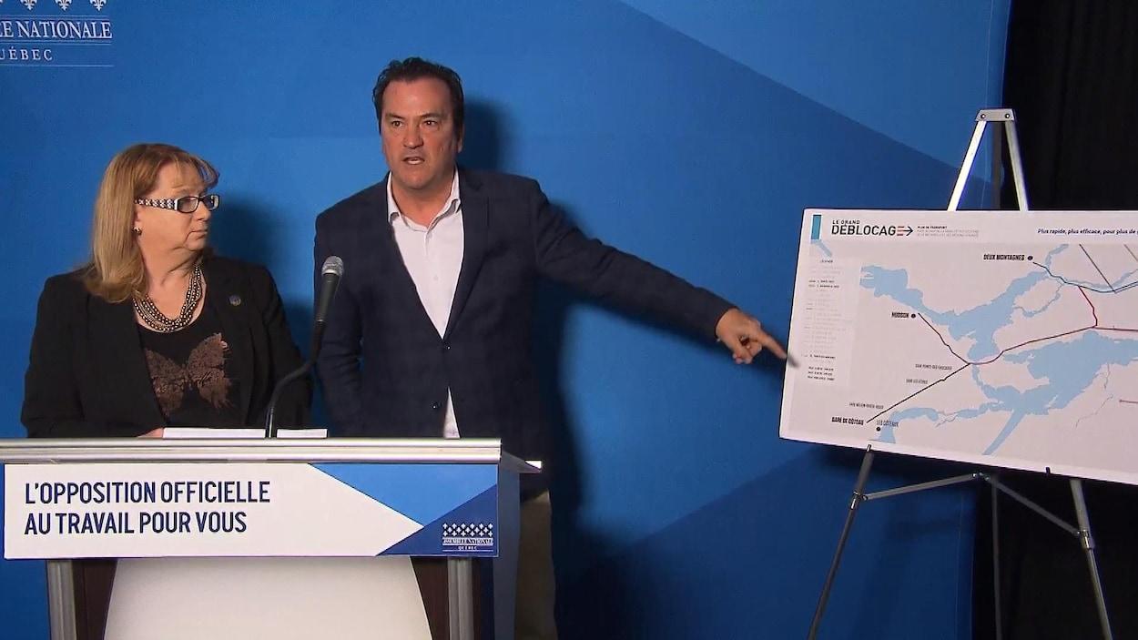 Alain Therrien pointe vers une carte de l'île de Montréal.