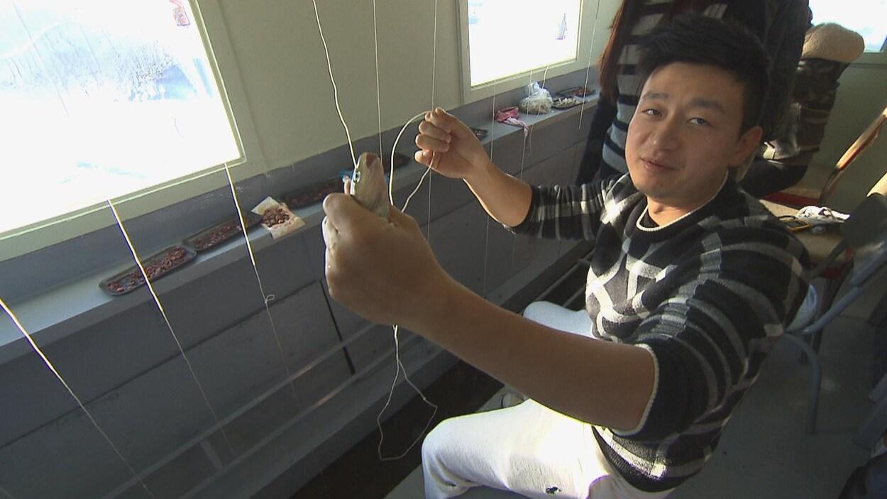 Un citoyen chinois tient dans une main un poulamon qu'il vient de pêcher.