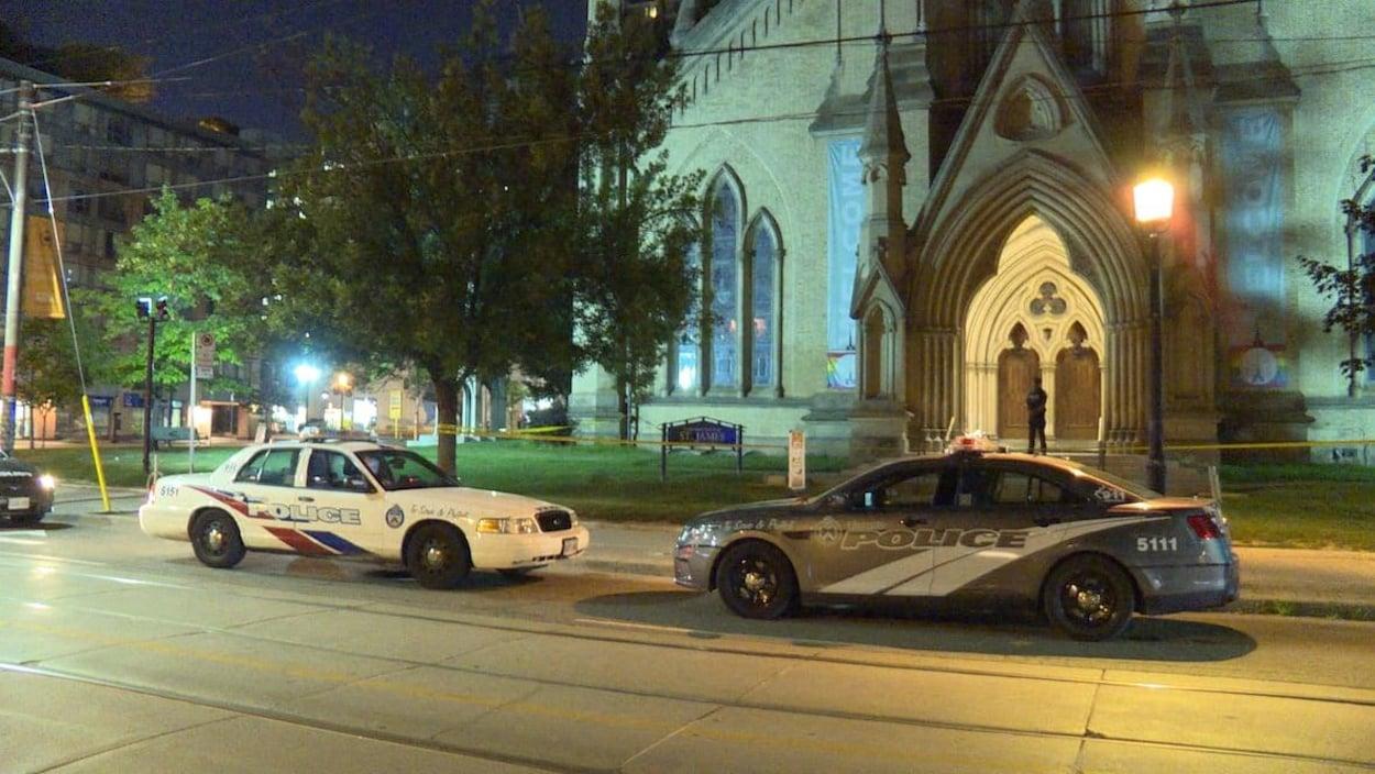 Deux voitures de police devant une cathédrale la nuit.