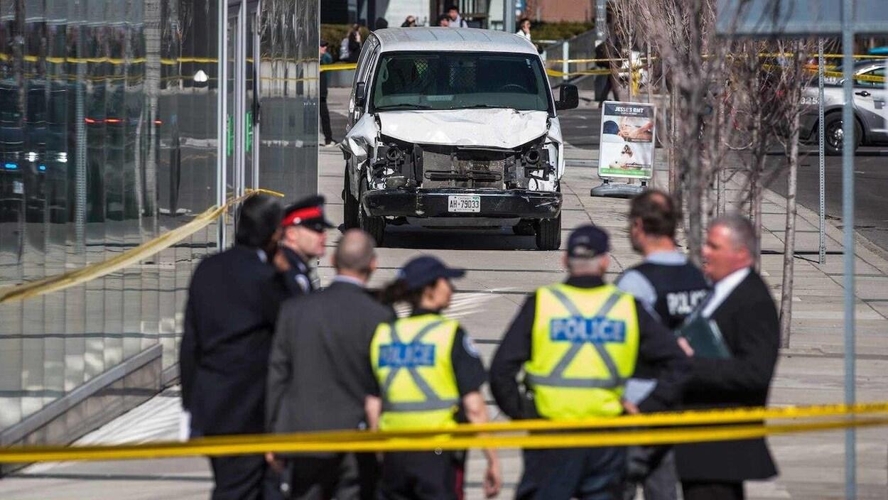 Des policiers en flou et le focus sur la fourgonnette blanche.
